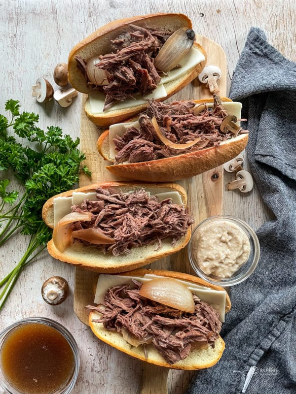 top view of french onion french dip sandwiches on wooden cutting board