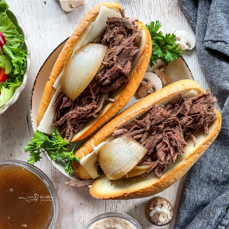 two french onion french dip sandwiches with onion