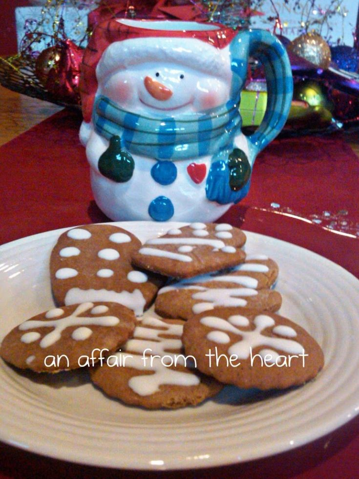 close up of Karen's Ginger Bread Cookies on a white plate and a snowman mug on a red surface