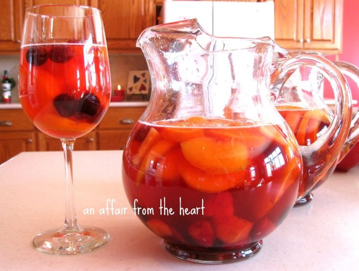 Pitchers of sangria and a tall wine glass with the sangria in it on a white table