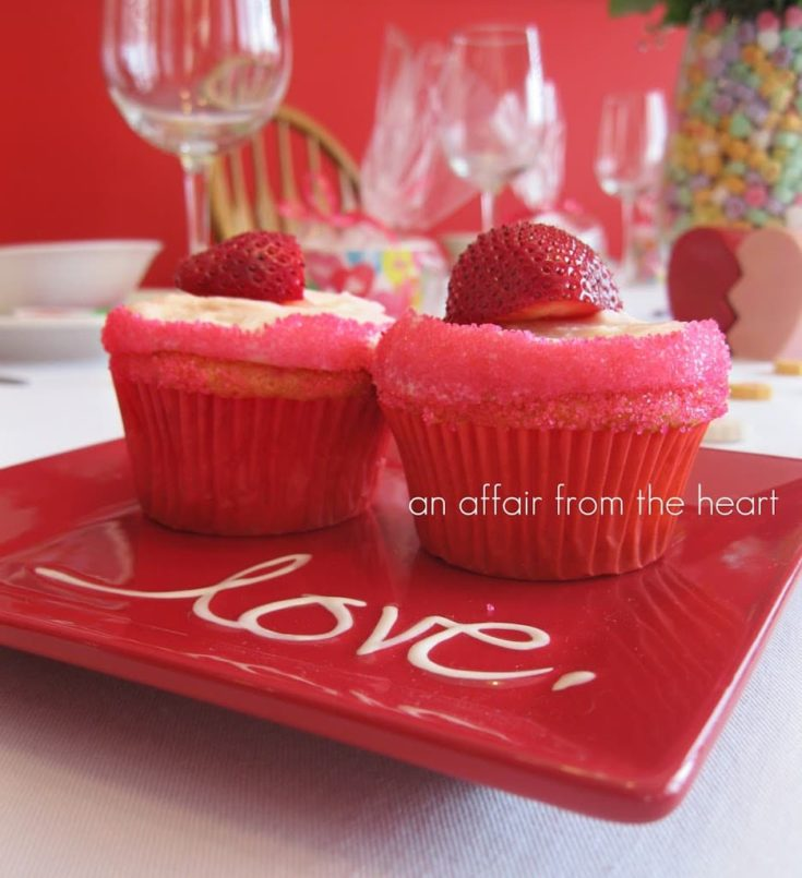 Side view of 2 Strawberry daiquiri cupcakes on a red plate that ahs the word love on it