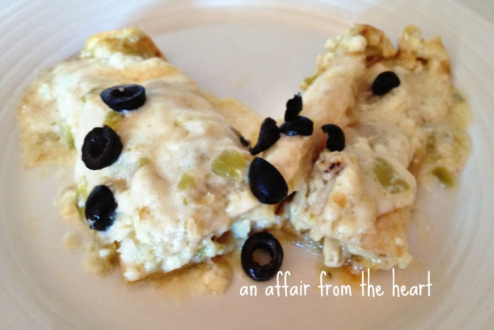 Enchiladas covered in sauce with olives on white plate