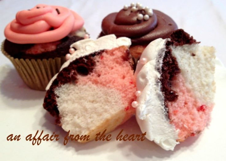 Neapolitan Cupcakes and one cut in half on a white surface