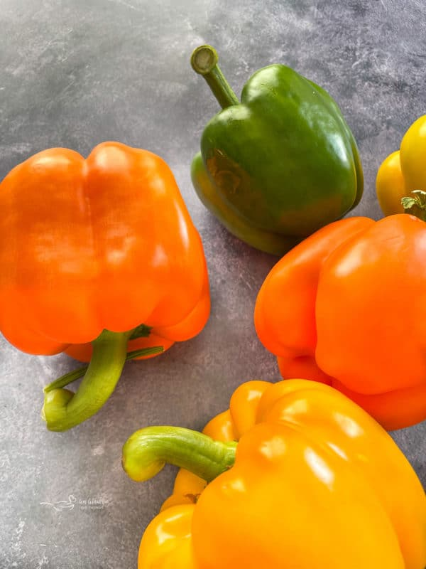 Four bell peppers in a variety of colors