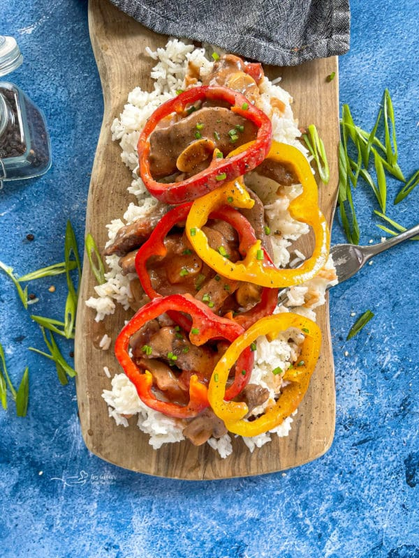 Steak, rice, and peppers on wooden surface