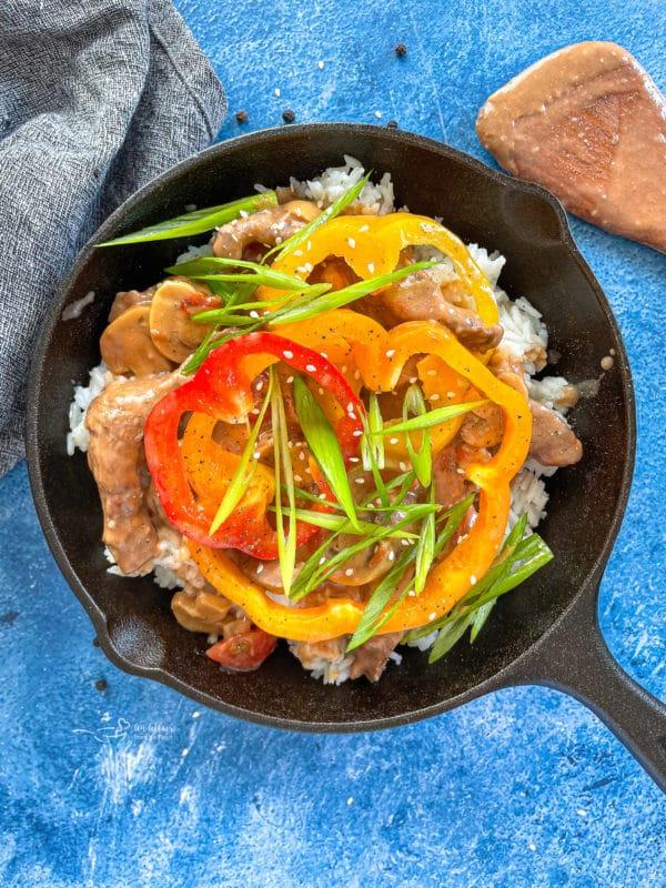 Top view of pepper steak in pan with veggies