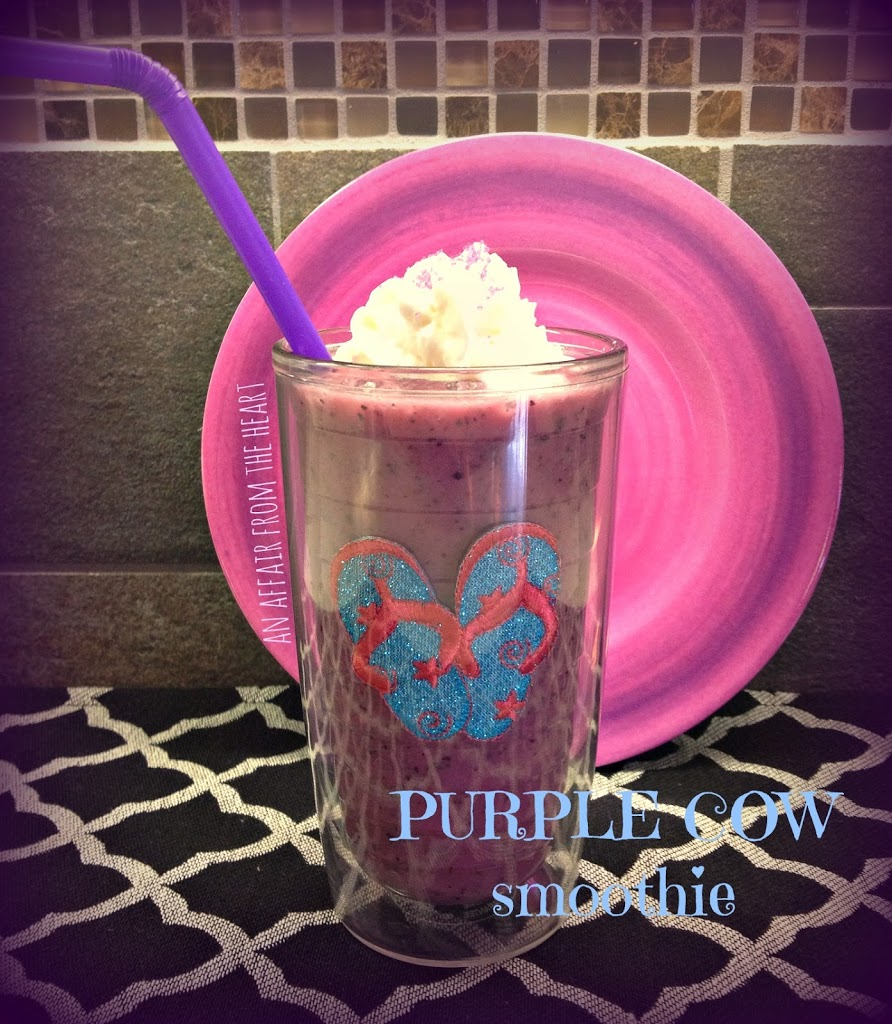 Front view of purple cow smoothie with straw and whipped cream