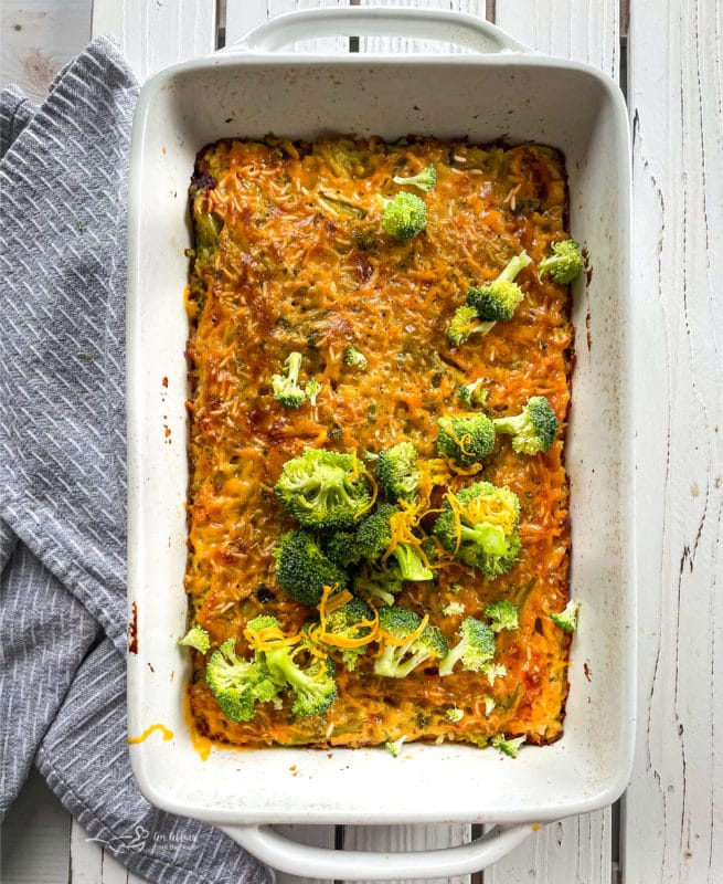 Top view of cooked broccoli and cheese casserole in a baking dish topped with broccoli