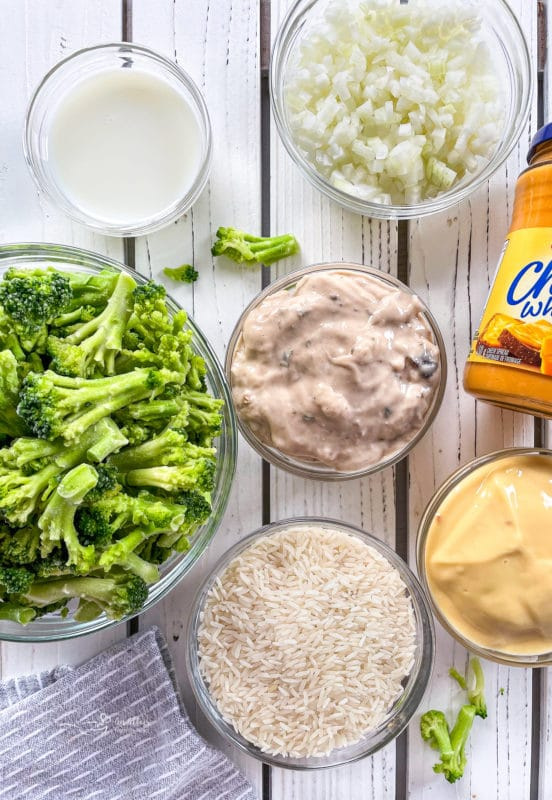Top view of cream of chicken, cream of mushroom, Cheese Whiz, rice, milk, onion, and broccoli