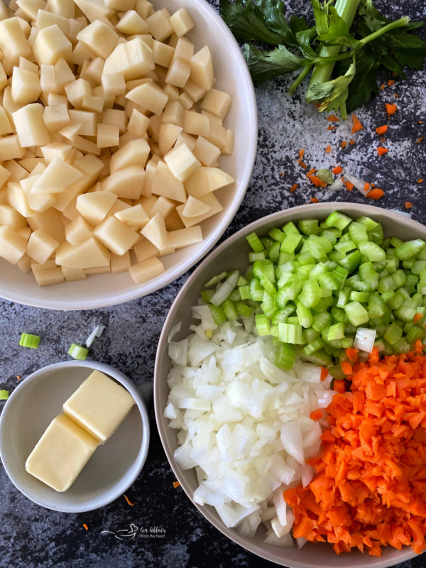 Top view of potatoes, onions, celery, carrots, and butter