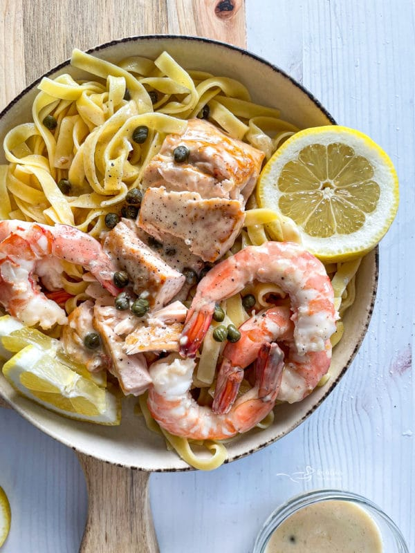 top view of lemon caper sauce over salmon and shrimp