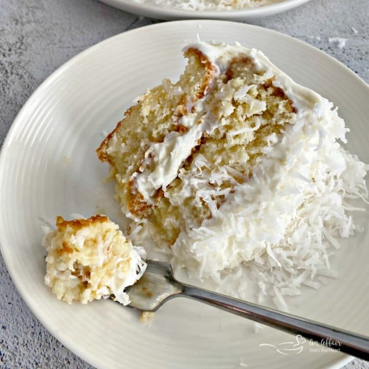 A fork with a bite of the COCONUT CREAM POKE CAKE WITH COCONUT WHIPPED CREAM FROSTING next to the slice of cake on a white plate