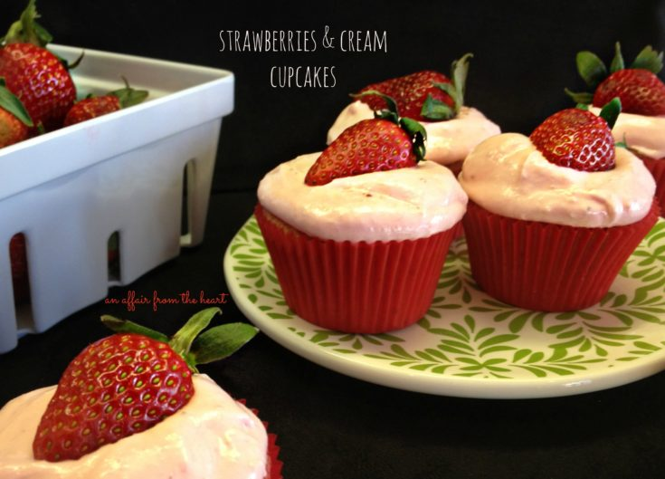 strawberries and cream cupcakes on a plate with leaves on it