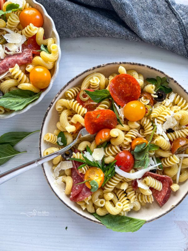 Two bowls of pasta salad with tomatoes and pepperoni