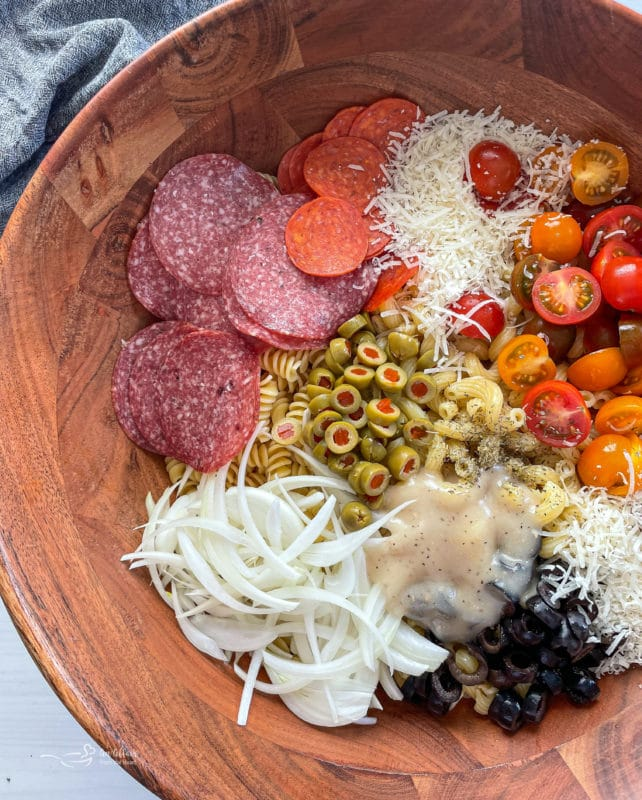 Bowl filled with salami, pepperoni, tomatoes, cheese, onions, olives, pasta, and dressing