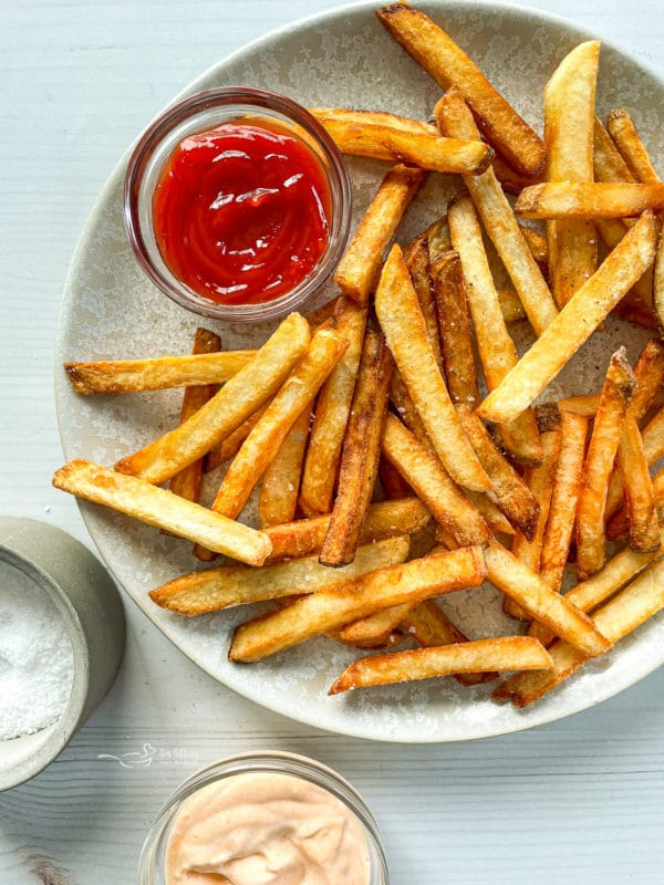 Top view of homemade double fried French fries on white plate with ketchup and salt