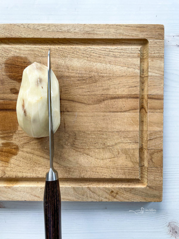 One peeled potato being sliced on wooden cutting board