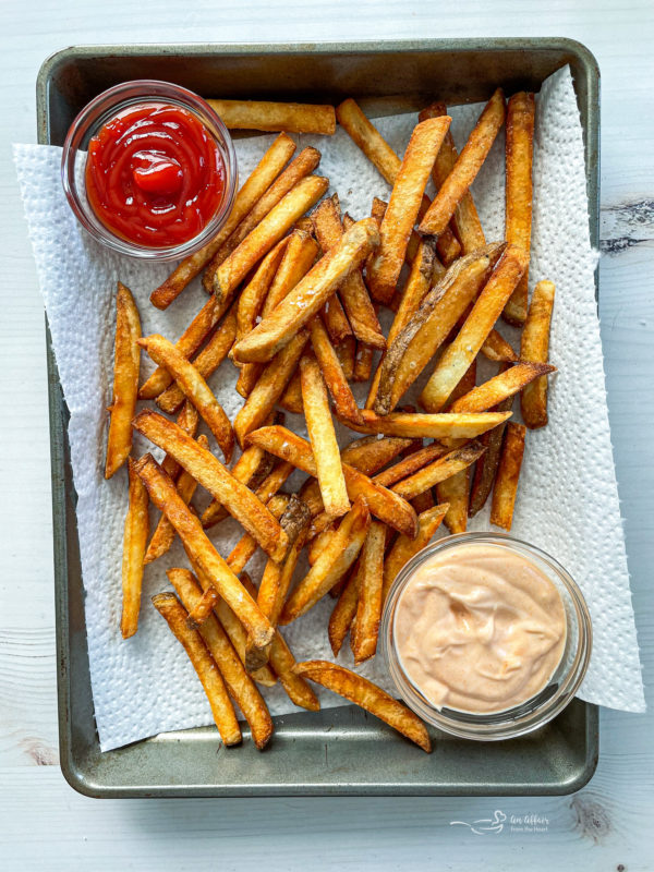Homemade double fried french fries on baking sheet with parchment paper, ketchup, and sauce