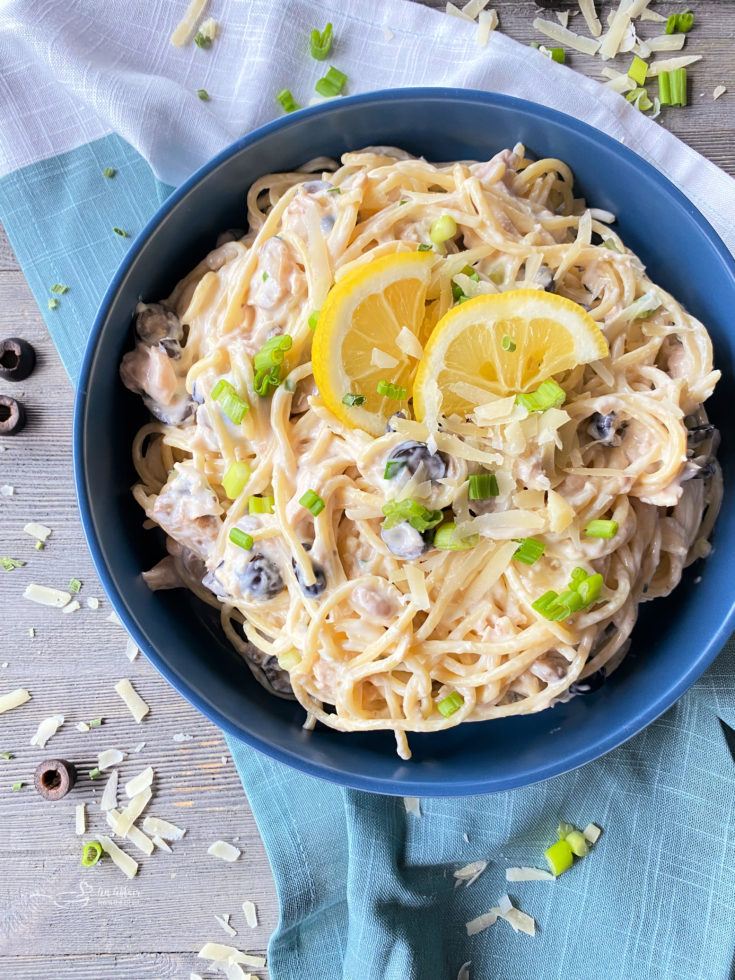 one bowl filled with pasta, tuna, mushrooms, olives, and lemon