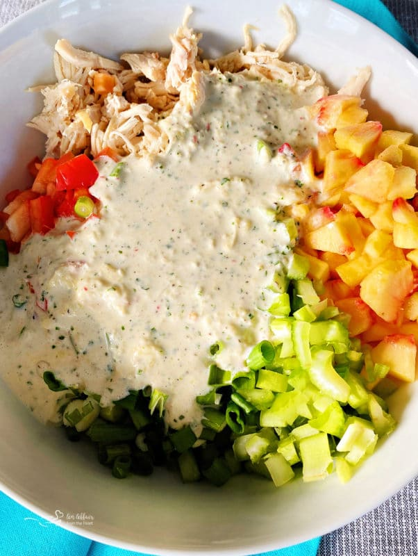 chopped ingredients and dressing in bowl with chicken