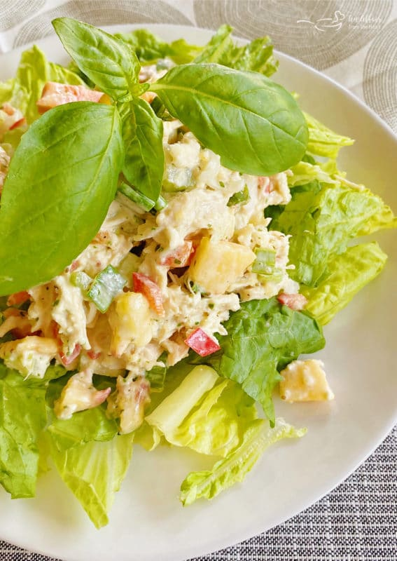 chicken salad on plate with basil and peach and lettuce