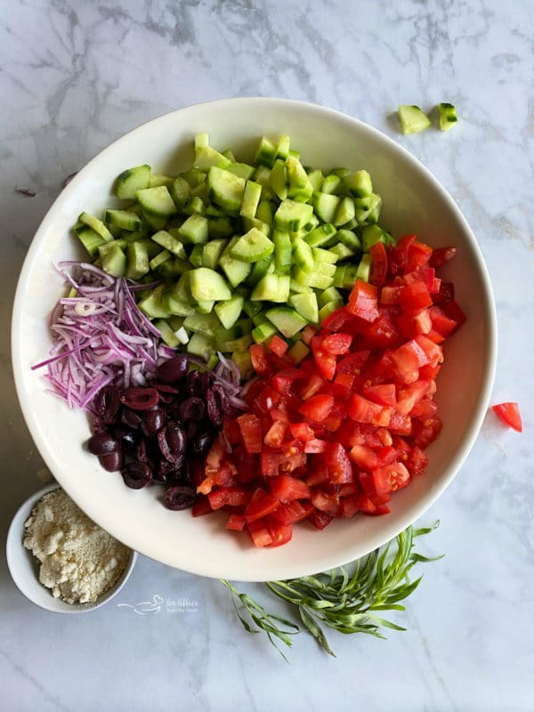 Tomatoes, olives, cucumbers, and red onion in a white bowl