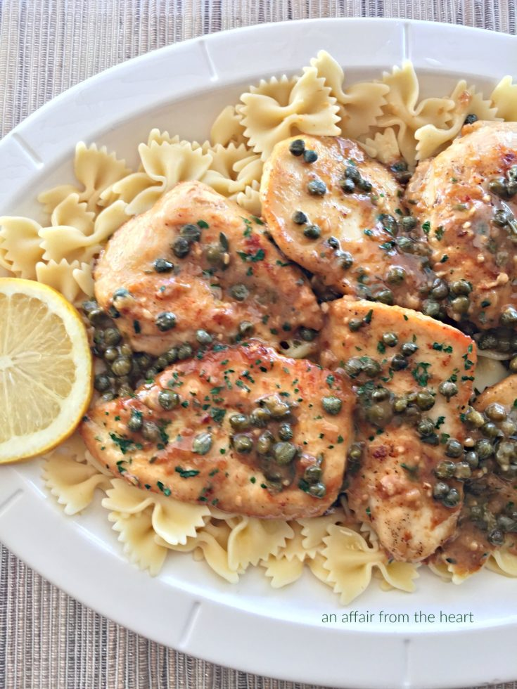 close up of Chicken Piccata and pasta on a white serving platter