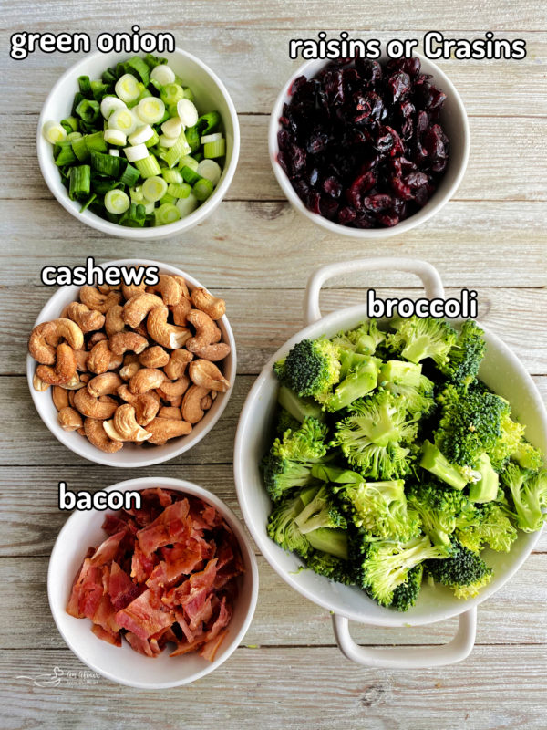 Wooden surface with cashews, green onion, raisins, broccoli, and bacon
