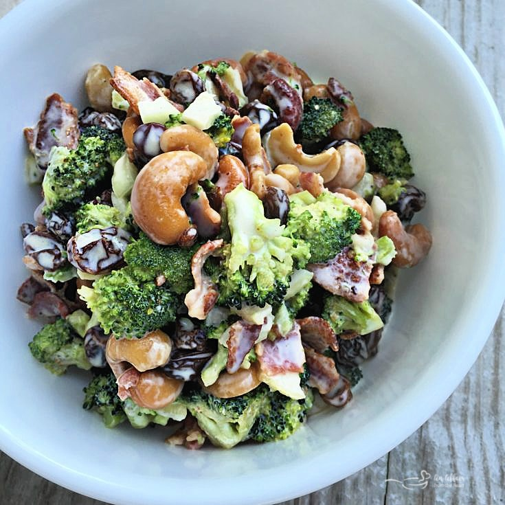 Top view bacon cashew broccoli salad in white bowl
