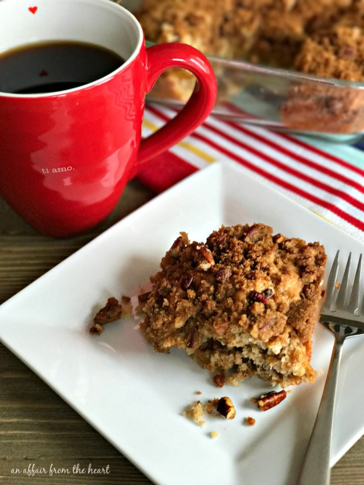 Cinnamon Crunch Coffee Cake on a white plate with a cup of coffee on a table