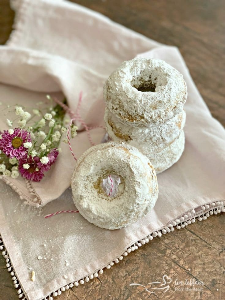 Baked Powdered Sugar Donuts stacked on a white napkin