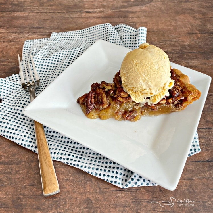 Slice of pecan pie with a scoop of ice cream on top on a white plate with a fork and polka dot napkin on a wood surface