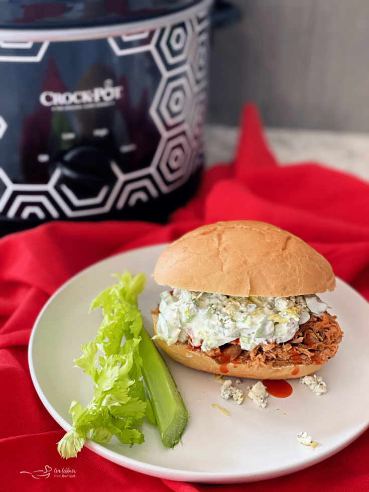 slow cooker buffalo pulled pork sandwich on white plate