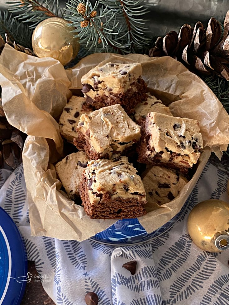 Chocolate Chip Cookie Dough Brownies in a cookie tin with evergreen and pinecones