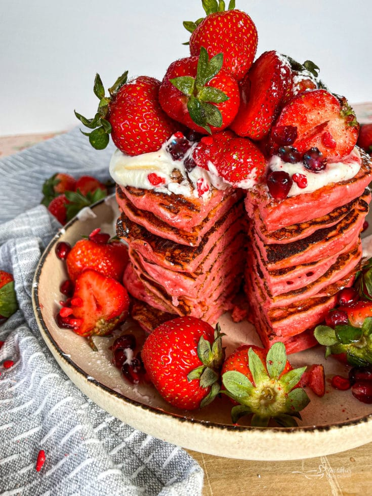 Close up of stacked Strawberry pancakes loaded with strawberries on top