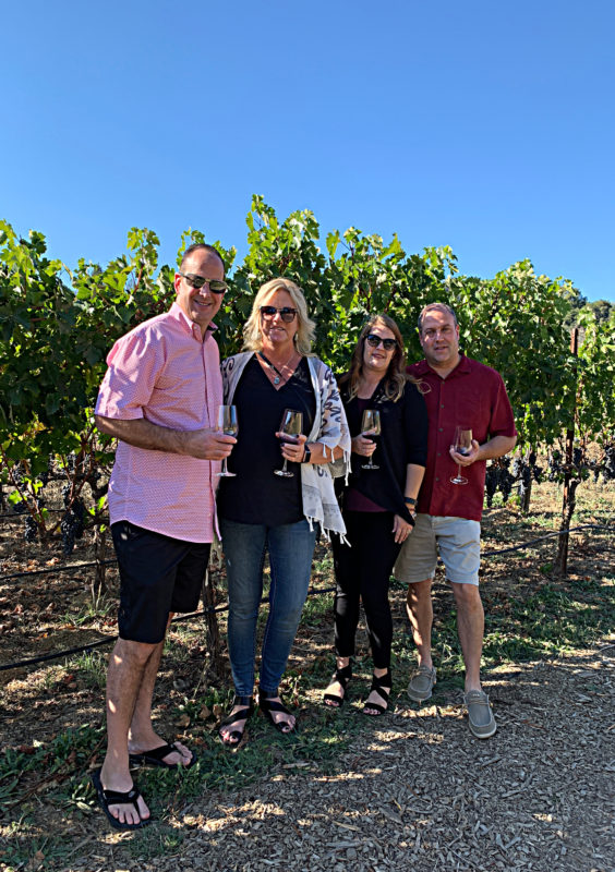 Four people standing in vineyard at Fontanella Winery