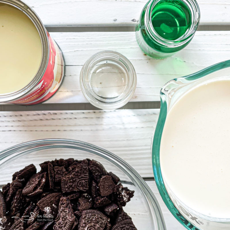 Top view of chopped Oreos, crème de cacao, crème de menthe, sweetened condensed milk, and heavy cream.