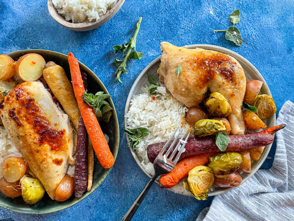 Two bowls of chicken with carrots, rice, potatoes, and Brussels sprouts