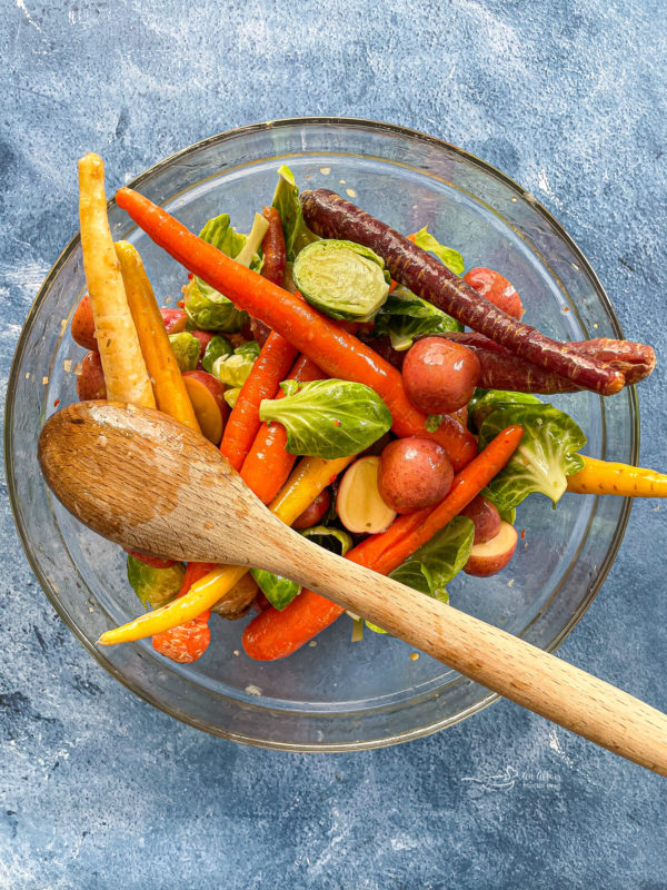 Carrots, potatoes, and Brussels sprouts in glass bowl with Italian dressing