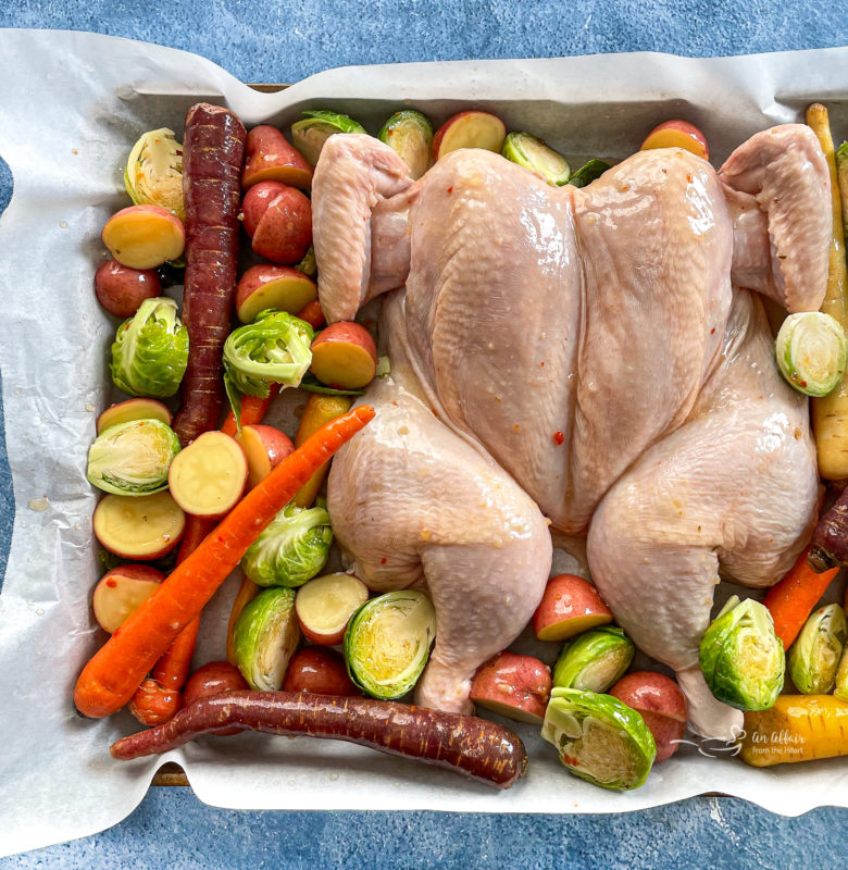 Top view of spatchcock chicken on baking sheet with carrots, Brussels sprouts, and potatoes