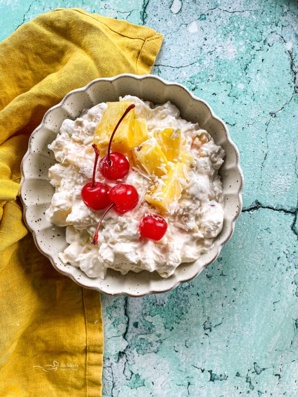 Bowl of pineapple fluff with cherries and diced pineapples