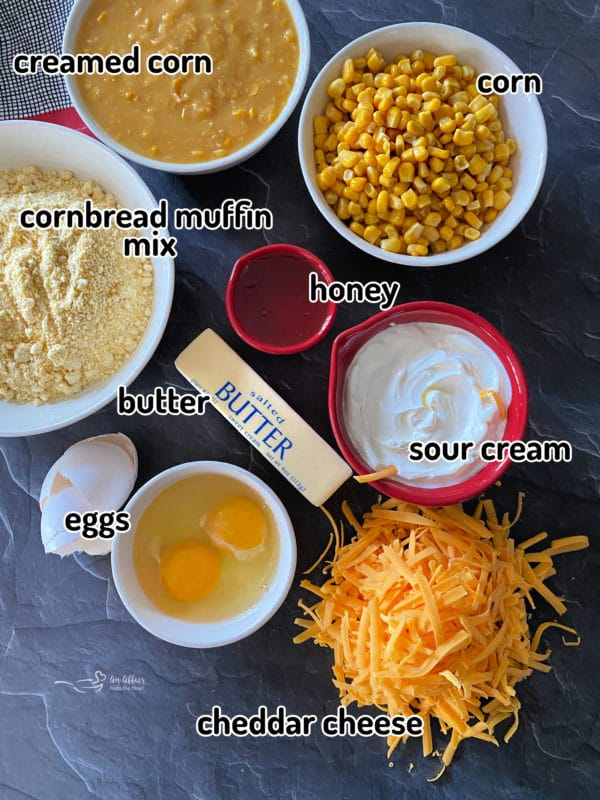 Creamed corn, cornbread muffin, butter, eggs, cheese, sour cream, and honey on grey surface
