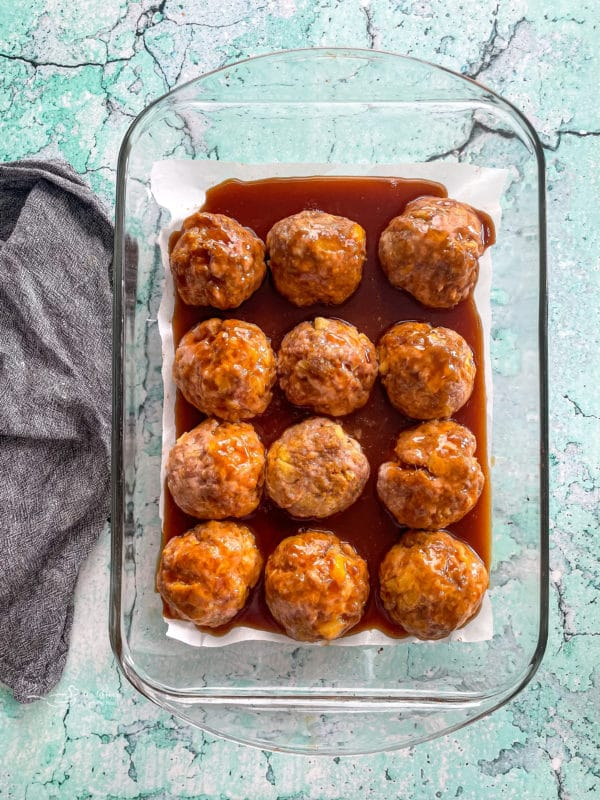 Top view of baked ham balls with sauce