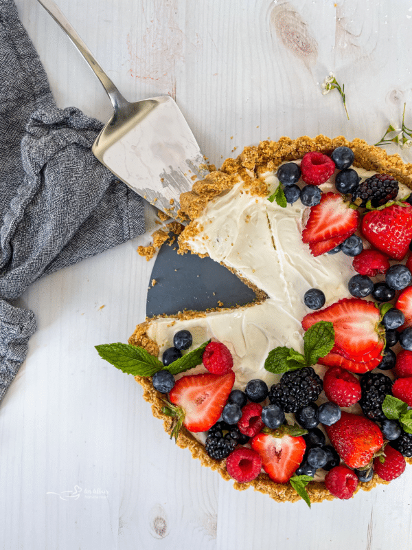 top view of one no bake fruit tart with fresh berries and mint
