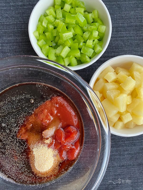 sauce ingredients in bowl with green onions and pineapple