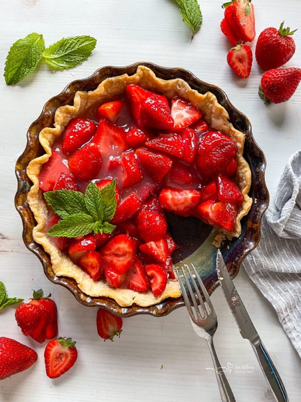 top view of fresh strawberry pie with fork and knife