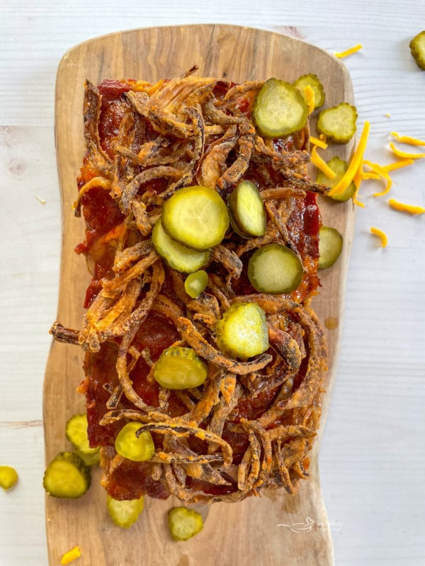 bacon cheeseburger meatloaf topped with fresh pickles and fried onions
