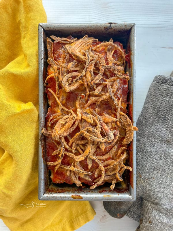 top view of meatloaf in pan with fried onions on top