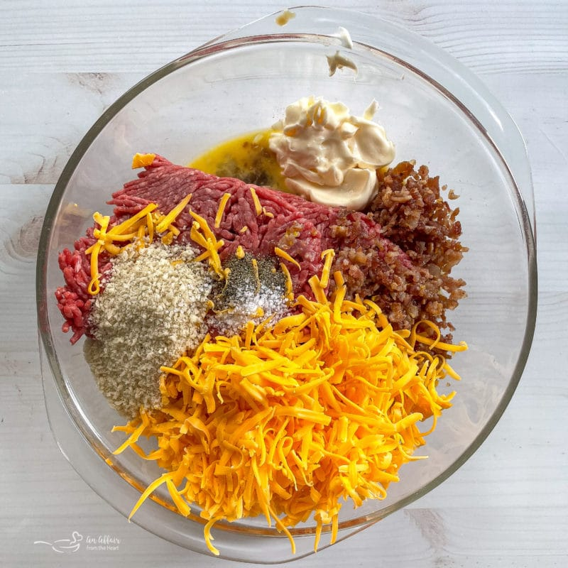 grated cheese, salt, pepper, breadcrumbs, meat, bacon, mayo, eggs, mustard in bowl