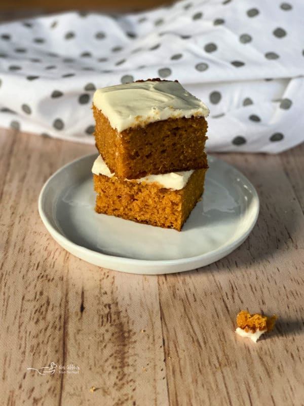 two carrot cake bars on white plate with cream cheese frosting